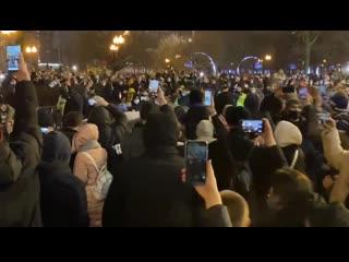 Протестующие заблокировали правительственную машину с мигалкой и начали бить ее ногами.