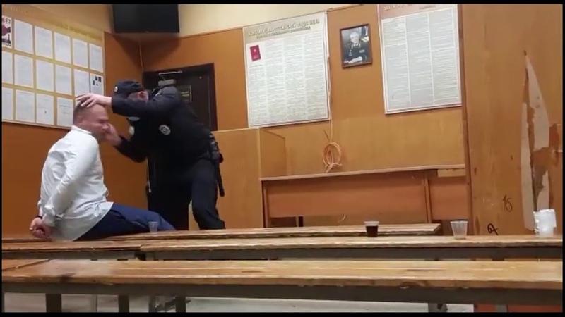 Сотрудник российской полиции бьёт человека в наручниках